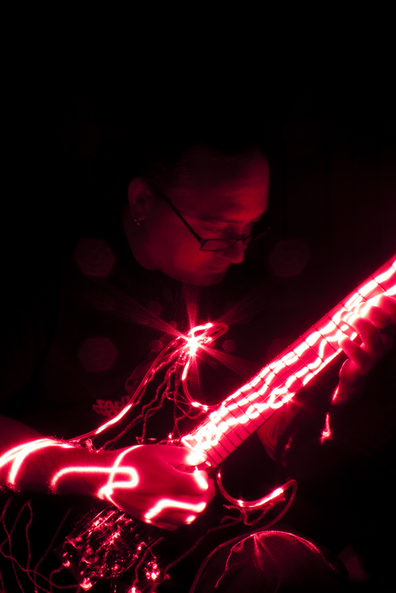 Henry Bale illuminated by guitar casting reflections of a laser pointer